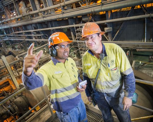 Melwyn Jerome, Safety Advisor, and Todd Allen, Operator (WorkPak) discuss workplace safety at the Zinc Lead Concentrator at Glencore's Mount Isa Mines. The photographer is Rob Parsons of Through The Looking Glass Studio. The image orientation is landscape.