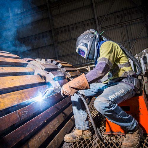 Nathan Brown, Boilermaker welding a loader bucket, Southern Cross Workshop. George Fisher Mine.